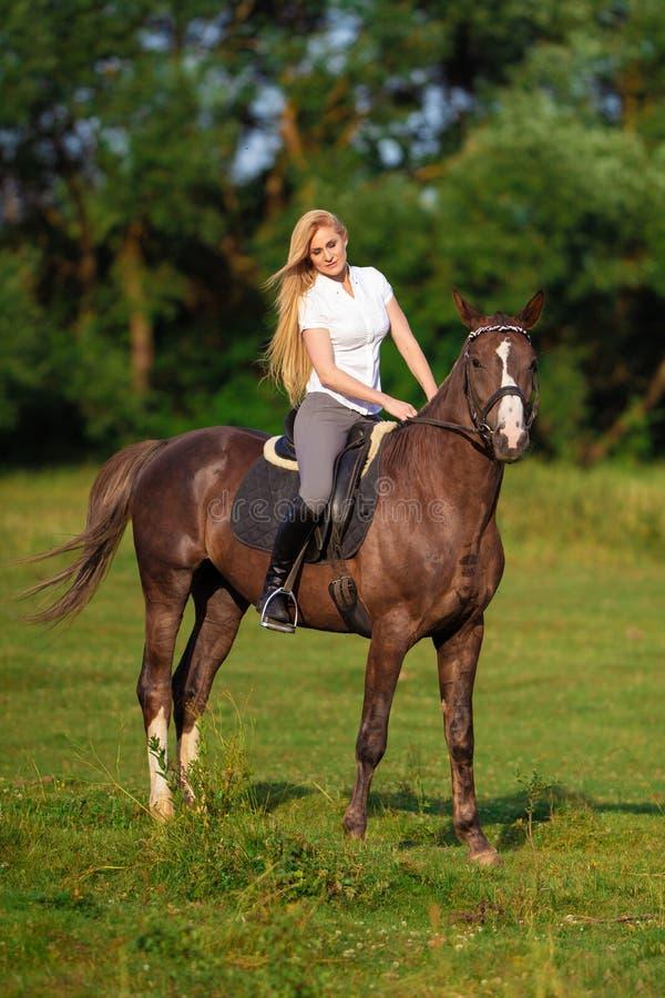 Ung blond kvinna med den långa hårjockeyryttaren som hoppar på en fjärdhäst royaltyfria foton