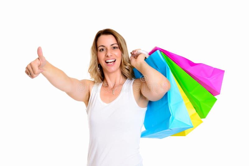 Ung blond kvinna med den shoppingpåsar och tummen upp royaltyfria bilder