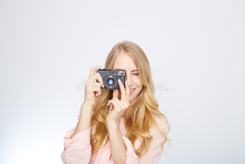 Ung blond kvinna med en tappningkamera arkivfoton