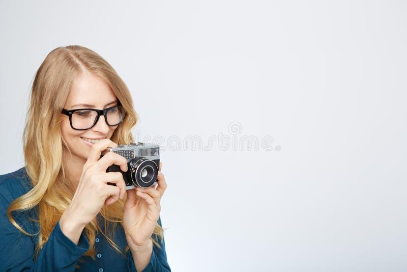 Ung blond kvinna med en tappningkamera arkivbilder