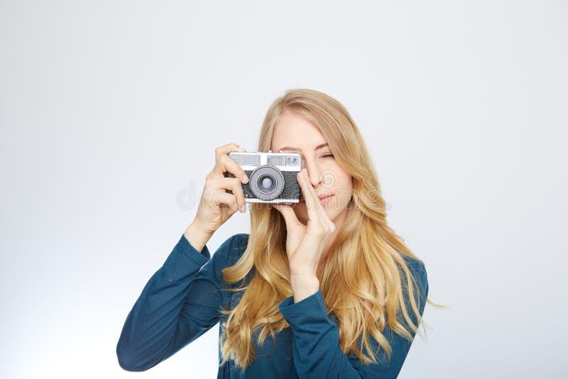 Ung blond kvinna med en tappningkamera fotografering för bildbyråer