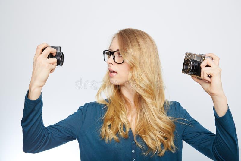 Ung blond kvinna med en tappningkamera arkivfoto