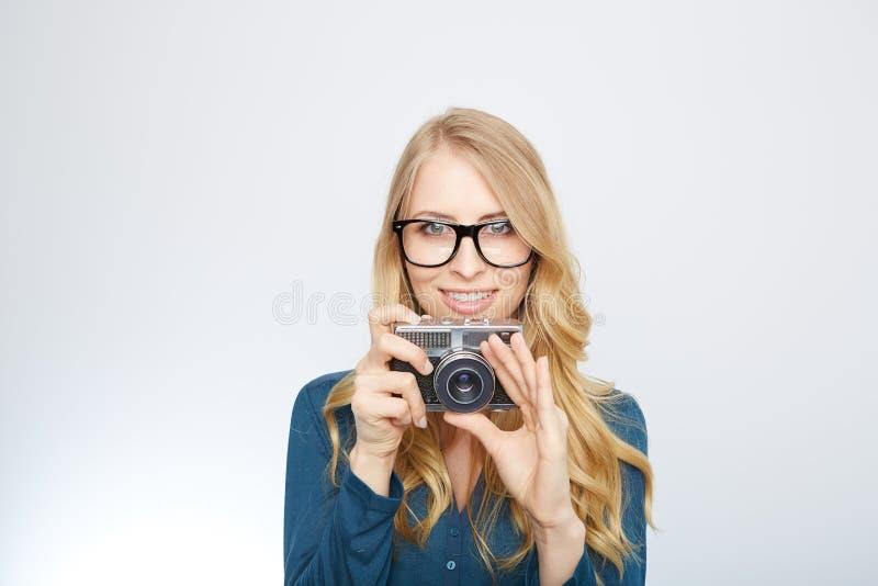 Ung blond kvinna med en tappningkamera royaltyfri foto