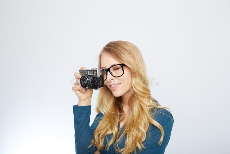 Ung blond kvinna med en tappningkamera royaltyfria foton