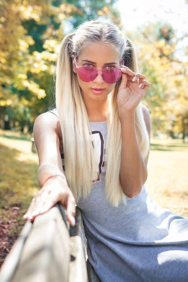 Ung blond kvinna med färgrik solglasögon som utomhus sitter på en bänk arkivbilder