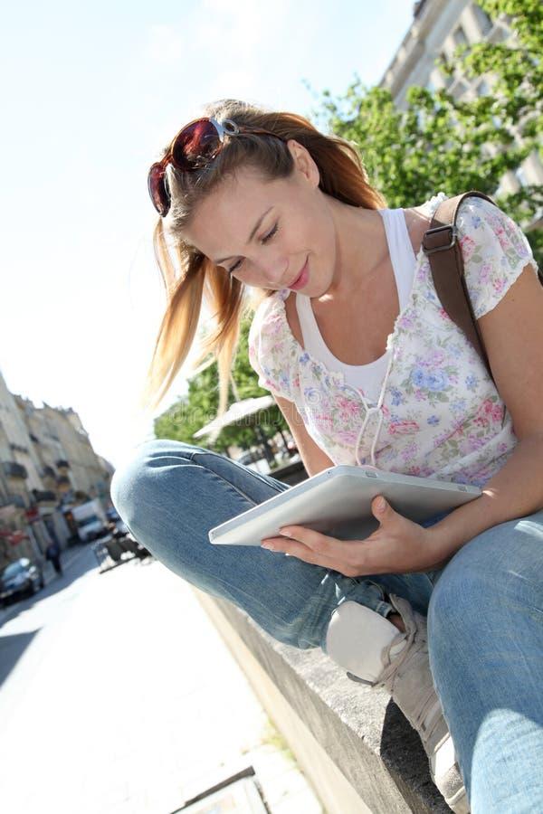 Ung blond kvinna med minnestavlan i stad royaltyfri foto