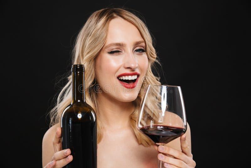 Ung blond kvinna med posera för kanter för ljus makeup som rött isoleras över svart väggbakgrund som dricker rött vin arkivbilder