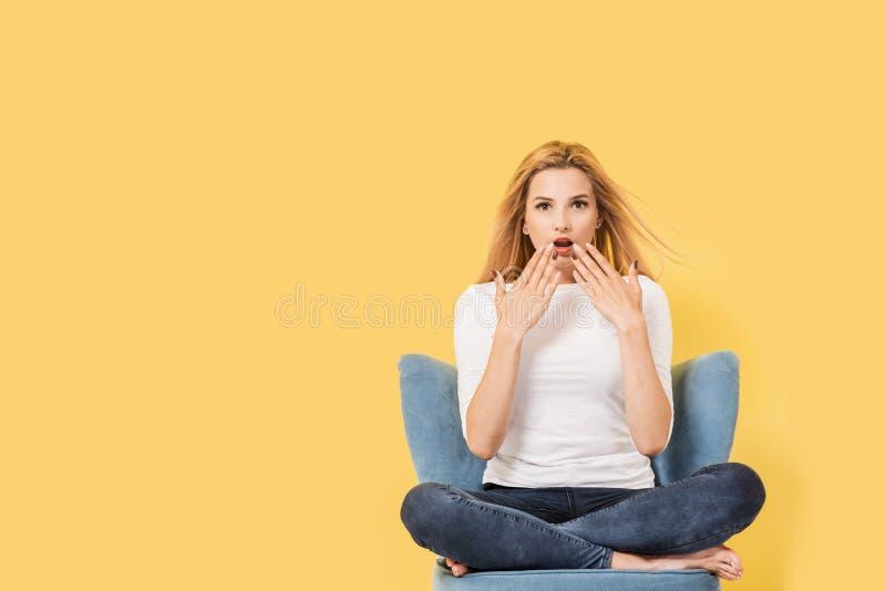 Ung blond kvinna på stol arkivbild
