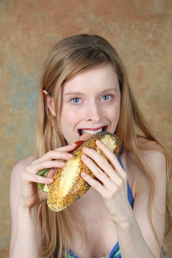 Ung blond kvinna som äter en smörgås royaltyfria foton