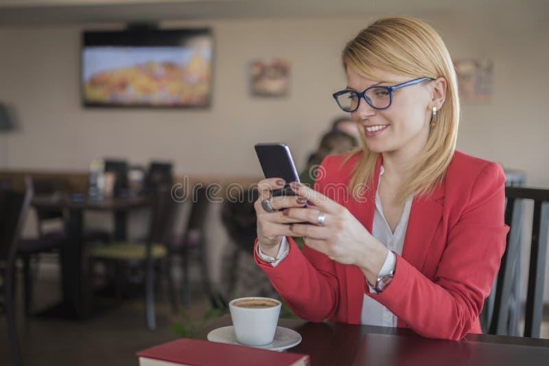 Ung blond kvinna som använder den smarta telefonen, texiting meddelande i kaffe arkivbild