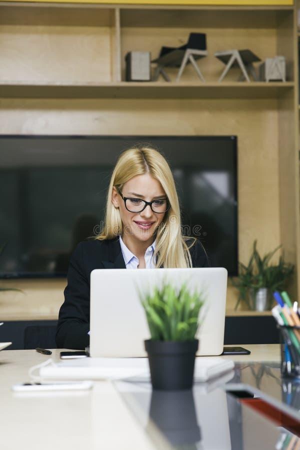 Ung blond kvinna som arbetar p? b?rbara datorn i kontoret royaltyfria bilder