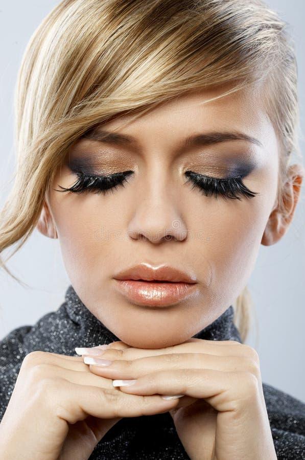 Ung blond kvinna som bär falska ögonfrans arkivfoton