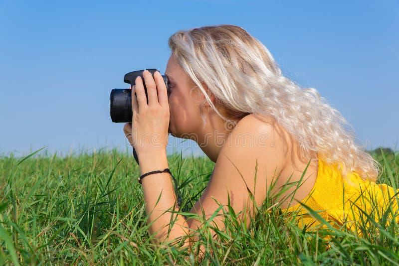 Ung blond kvinna som fotograferar i gräs royaltyfri foto