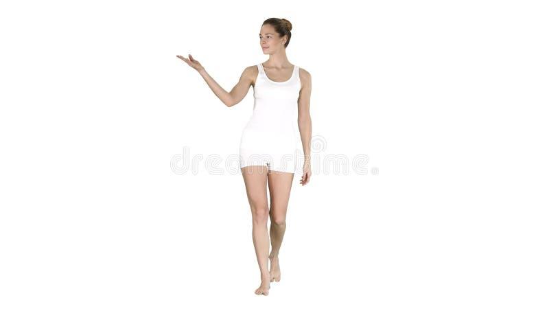 Ung blond kvinna som g?r och pekar till sidovisningen p? n?got p? vit bakgrund royaltyfria foton