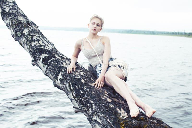 Ung blond kvinna som h?nger p? bj?rktr?d p? sj?kusten, utomhus- livsstil f?r sommarsemestrar arkivbilder