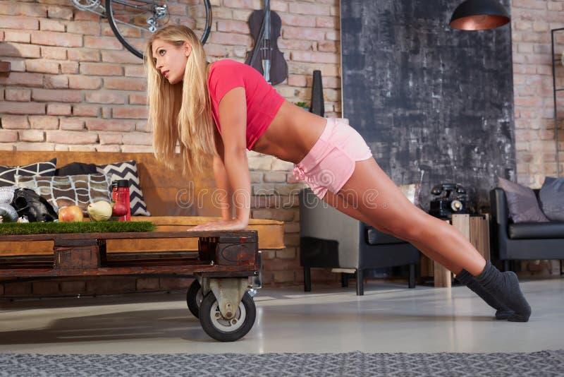 Ung blond kvinna som hemma gör konditionövning royaltyfria bilder