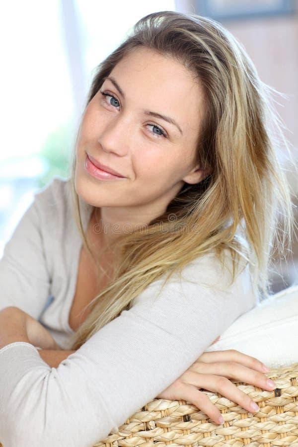 Ung blond kvinna som hemma kopplar av arkivfoton