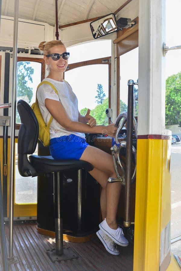 Ung blond kvinna som kör en spårvagn nummer 28 Berömd gul hissspårvagn arkivbild