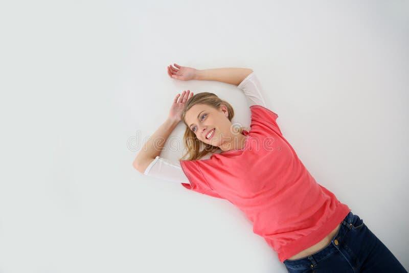 Ung blond kvinna som ler att ligga på golvet royaltyfri bild