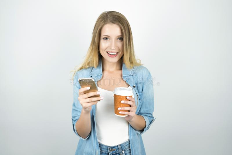 Ung blond kvinna som ler rymma smartphonen i en hand och kopp kaffe i en annan isolerad vit bakgrund arkivbild
