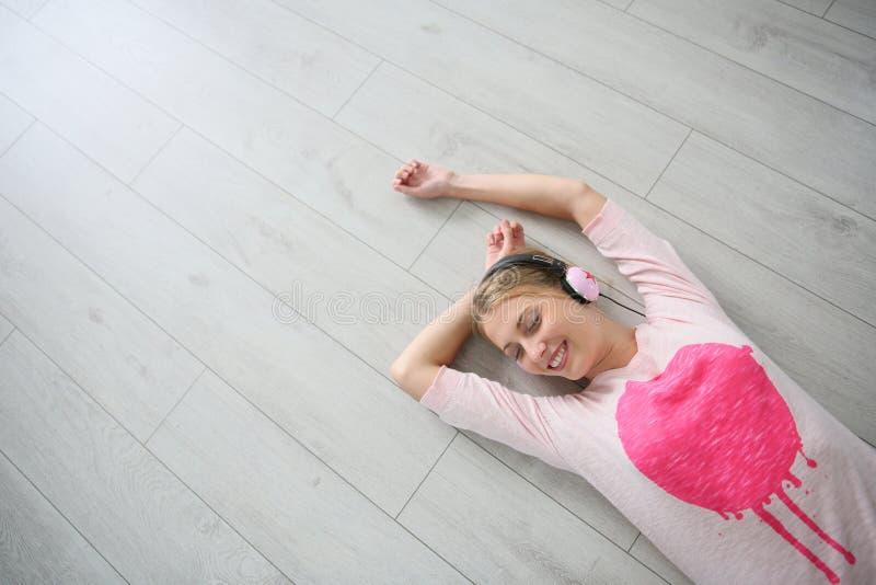 Ung blond kvinna som ligger på lyssnande musik för golv royaltyfri foto
