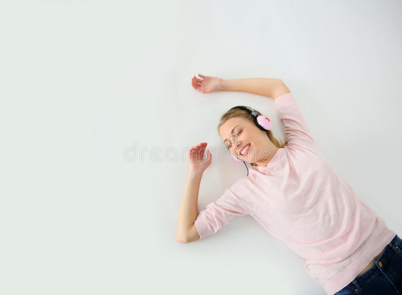 Ung blond kvinna som ligger på lyssnande musik för golv royaltyfri bild