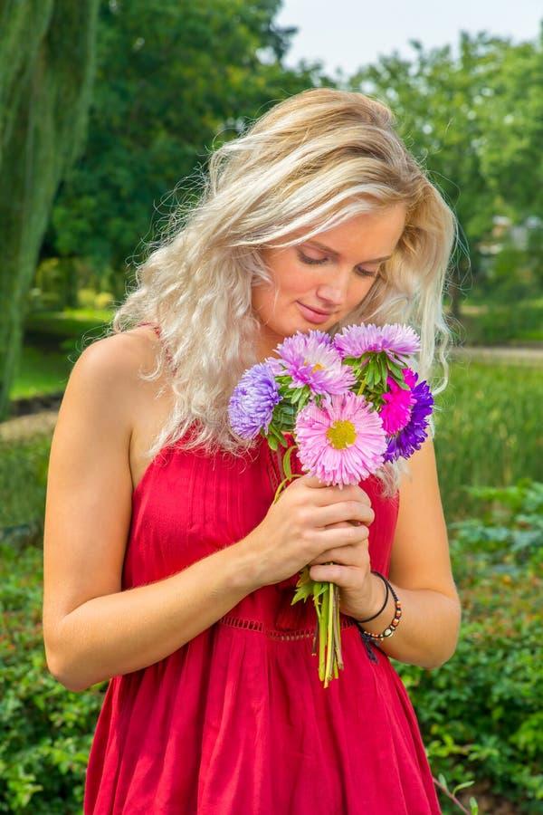 Ung blond kvinna som luktar sommarblommor royaltyfri bild