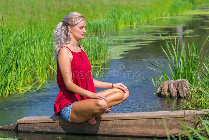 Ung blond kvinna som mediterar på vatten i natur royaltyfri fotografi