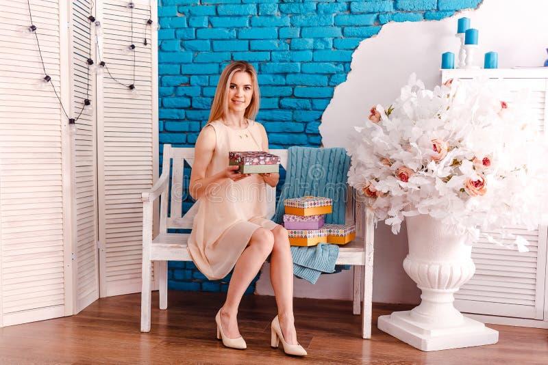 Ung blond kvinna som sitter på en bänk och rymmer gåvakartonger royaltyfri bild