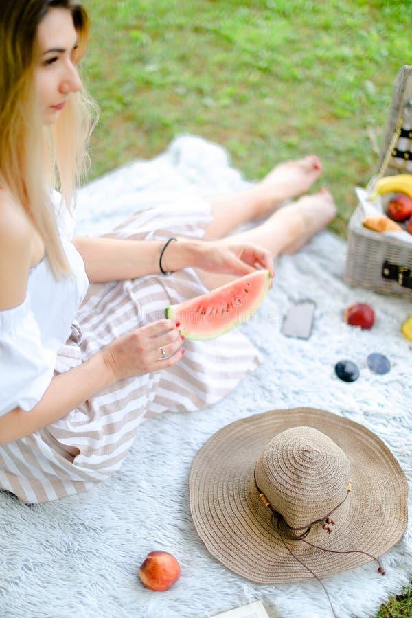 Ung blond kvinna som sitter på plädet nära frukter och hatten som äter vattenmelon, gräs i bakgrund royaltyfri foto