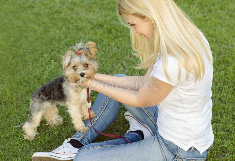 Ung blond kvinna som spelar med hennes hund arkivfoto