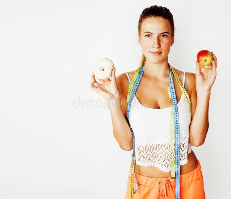 Ung blond kvinna som väljer mellan munken och äpplefruktisolat royaltyfri bild