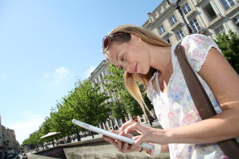 Ung blond kvinna som websurfing i stad royaltyfria foton