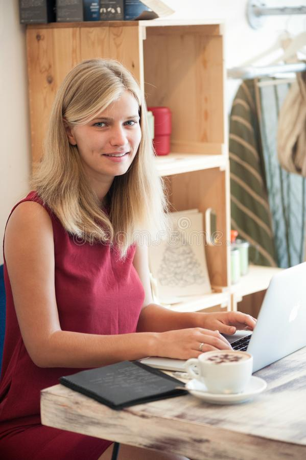 Ung blond kvinnamaskinskrivning i bärbar dator i kafé royaltyfria foton