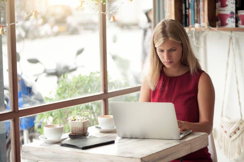 Ung blond kvinnamaskinskrivning i bärbar dator i kafé royaltyfri bild
