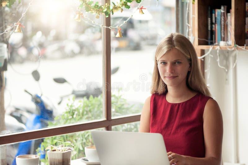 Ung blond kvinnamaskinskrivning i bärbar dator i kafé royaltyfri fotografi