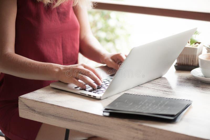 Ung blond kvinnamaskinskrivning i bärbar dator i kafé royaltyfri foto