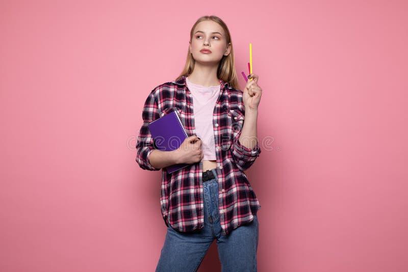 Ung blond kvinnlig student i tillf?llig kl?der som rymmer den purpurf?rgade anteckningsboken och pennan i hennes hand arkivbilder