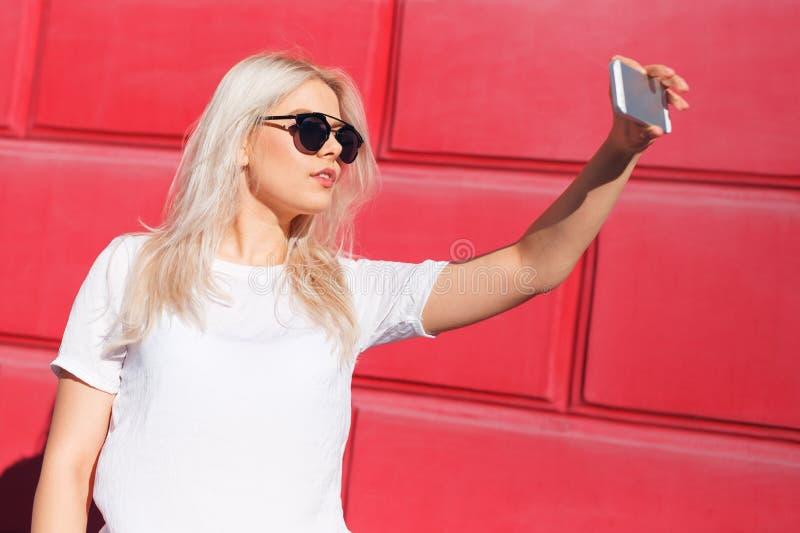 Ung blond kvinnlig vlogger med smartphonen royaltyfria bilder