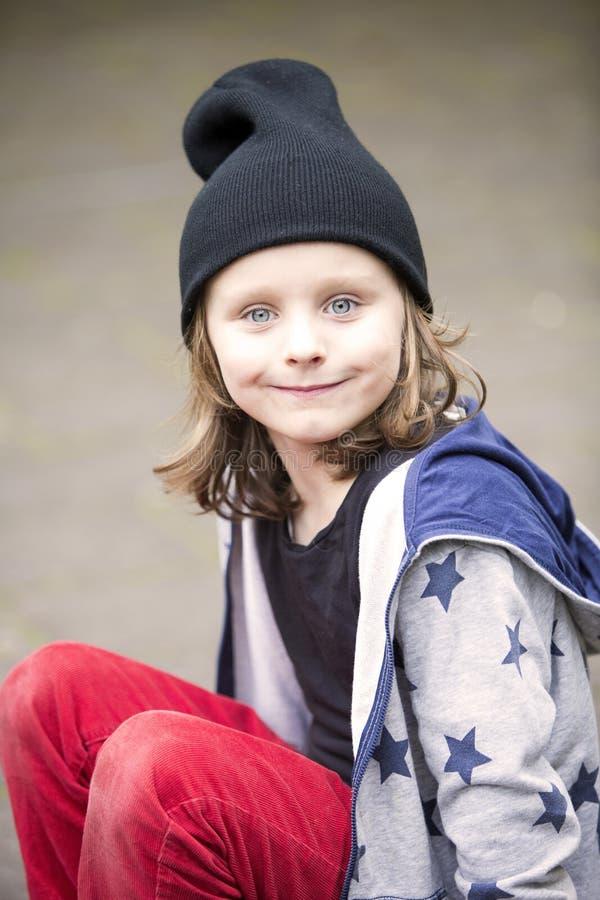 Ung blond långhårig pojke i röda flåsanden arkivfoto