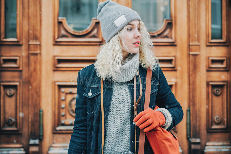 Ung blond lockig flicka med röda handskar och påsen, vinter royaltyfria foton
