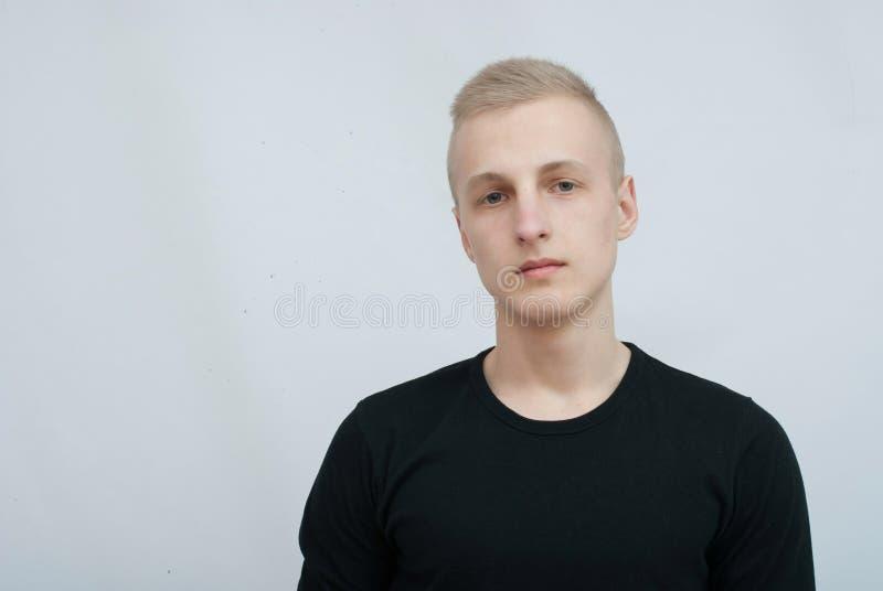 Ung blond manstående i studio på grå bakgrund arkivfoto