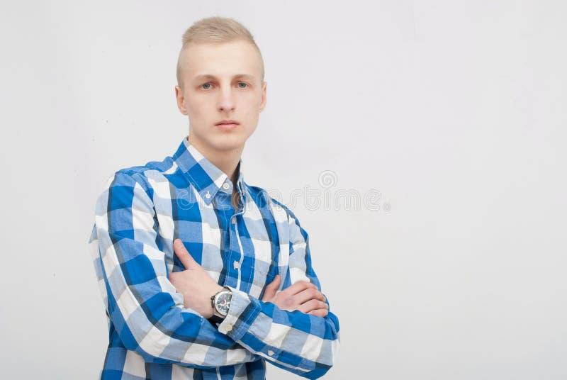 Ung blond manstående i studio på grå bakgrund arkivfoton