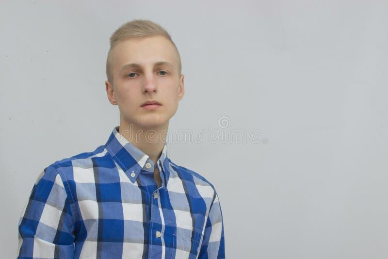 Ung blond manstående i studio på grå bakgrund royaltyfri bild