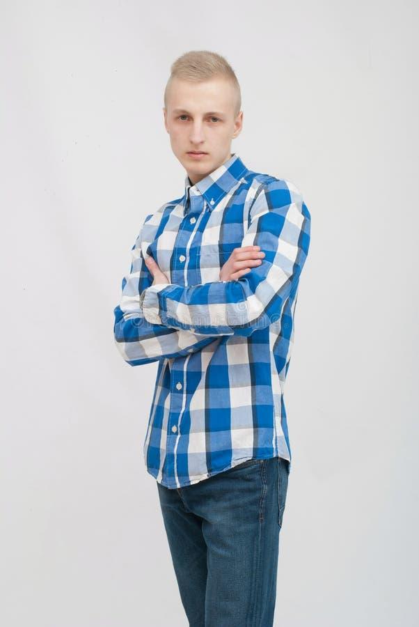 Ung blond manstående i studio på grå bakgrund arkivbilder