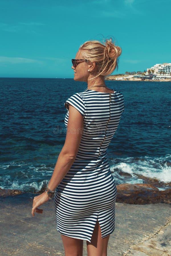 Ung blond medelhavs- kvinna som poserar på den steniga kusten arkivfoton