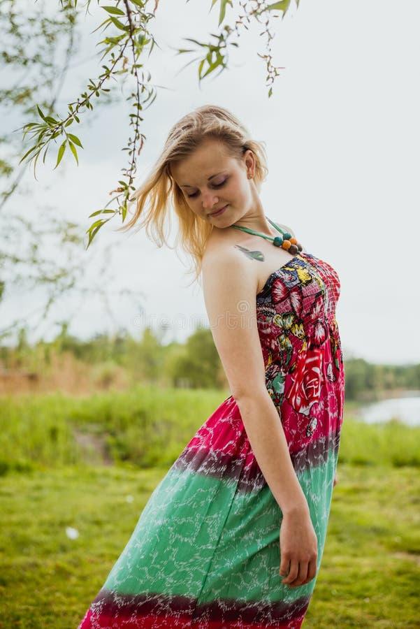 Ung blond nätt dam i gröna och röda sundress arkivbild