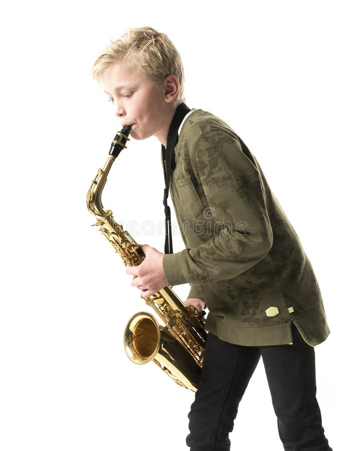 Ung blond pojke och saxofon i studio arkivbild