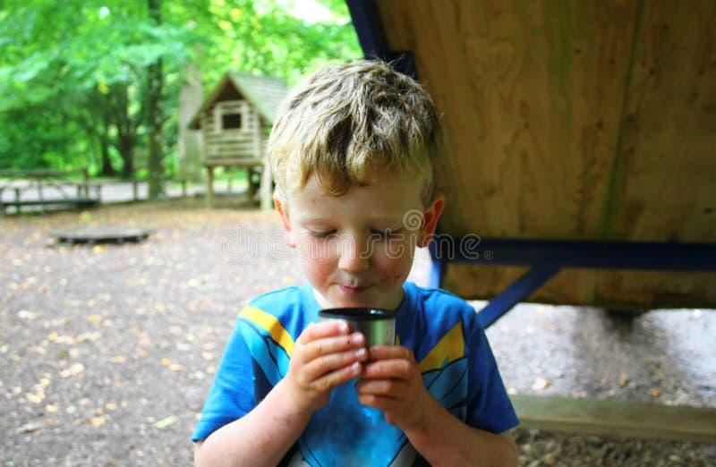 Ung blond pojke som dricker kopp te - som är våt som är smutsig som är smutsig som är nedsmutsad och som är lycklig royaltyfri fotografi
