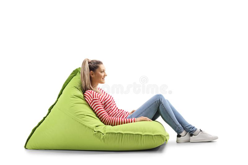 Ung blond tillfällig kvinna som sitter på en haricot vertpåse arkivfoto